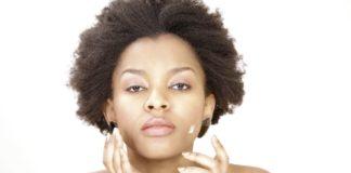 Dzaleu Beauté Nianga fille-en-afro-mettant-crème-visage.